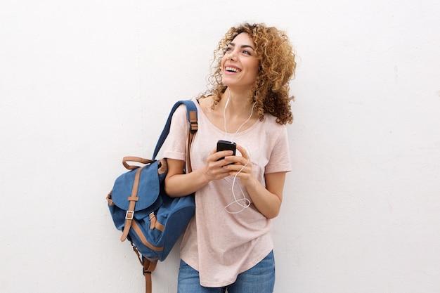 Heureuse jeune femme écoutant de la musique avec des écouteurs par mur blanc