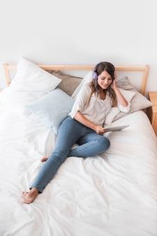 Heureuse jeune femme écoutant de la musique sur le lit