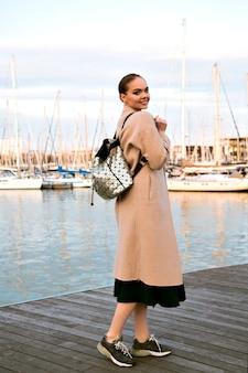 Heureuse jeune femme élégante marchant au yacht club de luxe de barcelone, portant des baskets et sac à dos, mi-saison touristique.