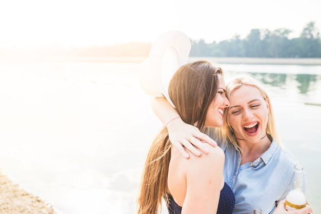 Heureuse jeune femme embrassant son amie debout près du lac