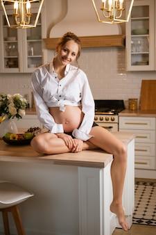 Heureuse jeune femme enceinte en chemise blanche est assise à table dans la cuisine