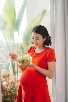 Heureuse jeune femme enceinte, manger une salade de légumes et souriant près de la fenêtre à la maison