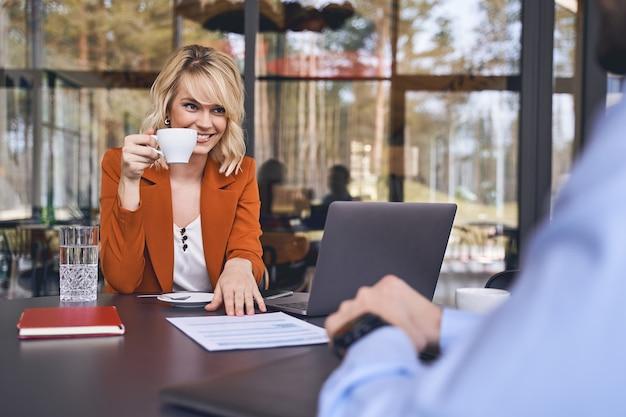 Heureuse jeune femme entrepreneur avec une tasse de café assise devant son partenaire commercial