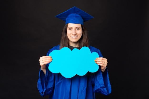 Heureuse jeune femme étudiante portant baccalauréat et tenant un nuage bleu vide