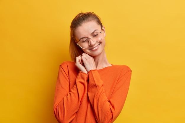 Heureuse jeune femme européenne avec une expression heureuse ferme les yeux et sourit en inclinant doucement la tête