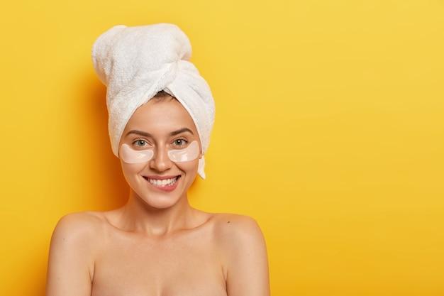 Heureuse jeune femme européenne positive mord les lèvres, regarde joyeusement la caméra, porte des patchs cosmétiques sous les yeux, se tient torse nu sur fond jaune, espace vide
