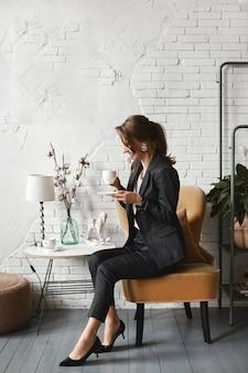 Heureuse jeune femme européenne souriante et buvant un thé dans un intérieur vintage fille modèle joyeuse dans un costume à la mode buvant du café à l'intérieur du café