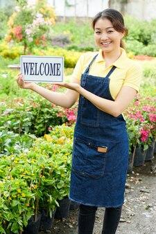Heureuse jeune femme excitée montrant un signe de bienvenue lorsqu'elle se tient dans l'île entre des pots de fleurs au marché aux plantes