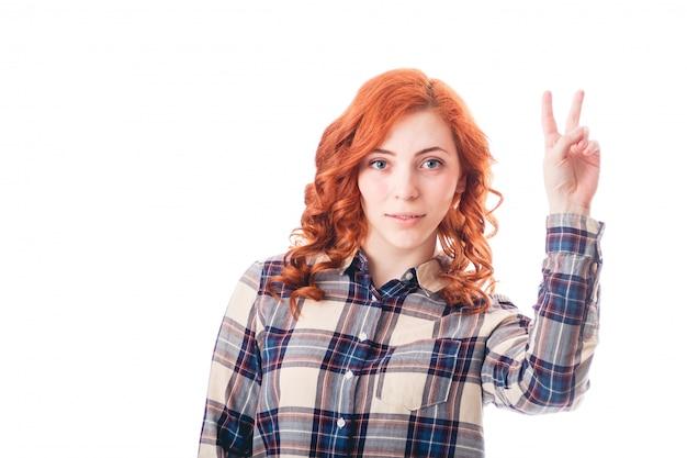 Heureuse jeune femme excitée montrant le signe de la victoire