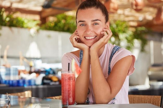 Heureuse jeune femme avec une expression satisfaite, a un look attrayant, garde les mains sous le menton, est détendue et passe du temps libre dans un restaurant confortable, boit des boissons fraîches, passe des vacances d'été sous les tropiques