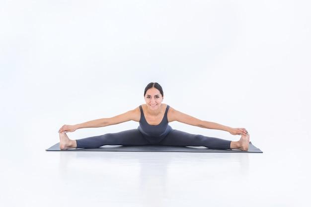 Heureuse jeune femme faisant du yoga stretch sur tapis sur fond blanc