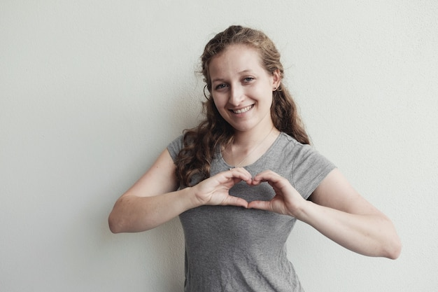 Heureuse jeune femme faisant ses mains en forme de coeur