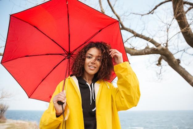 Heureuse jeune femme frisée africaine portant un manteau jaune avec parapluie.