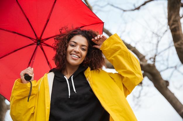 Heureuse jeune femme frisée africaine portant un manteau jaune avec parapluie