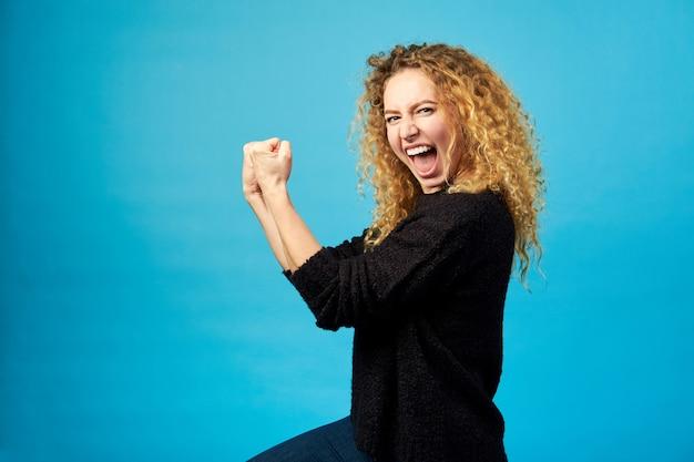 Heureuse jeune femme frisée rousse fêtée et acclamant un succès en frappant l'air avec ses poings sur le mur bleu