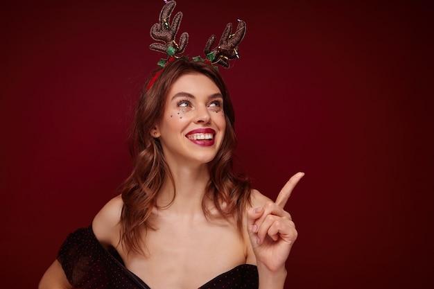 Heureuse jeune femme gaie aux cheveux bruns avec un maquillage festif et des étoiles d'argent sur son visage montrant joyeusement vers le haut avec l'index, profitant d'une soirée à thème de noël