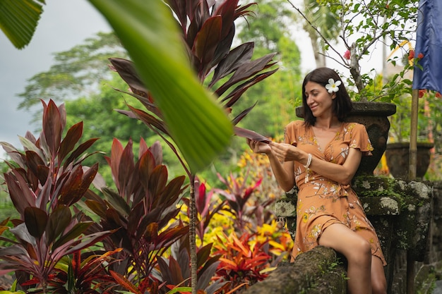 Heureuse jeune femme gardant le sourire sur son visage tout en regardant des plantes exotiques pendant le tournage