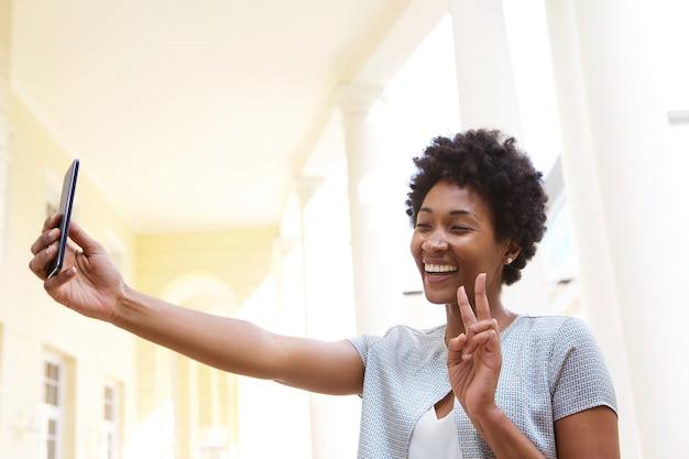 Heureuse jeune femme gesticulant un signe de paix et prenant selfie