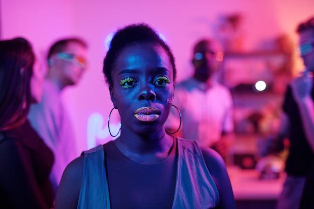 Heureuse jeune femme glamour d'origine africaine dans des vêtements décontractés intelligents en gardant les yeux fermés tout en se tenant devant ses amis danseurs