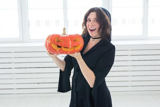 Heureuse jeune femme gothique en costume de sorcière halloween souriant sur salle blanche