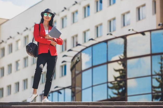 Heureuse jeune femme hipster travaillant sur un ordinateur portable extérieur. fille étudiante à l'aide d'un ordinateur portable sur le campus universitaire