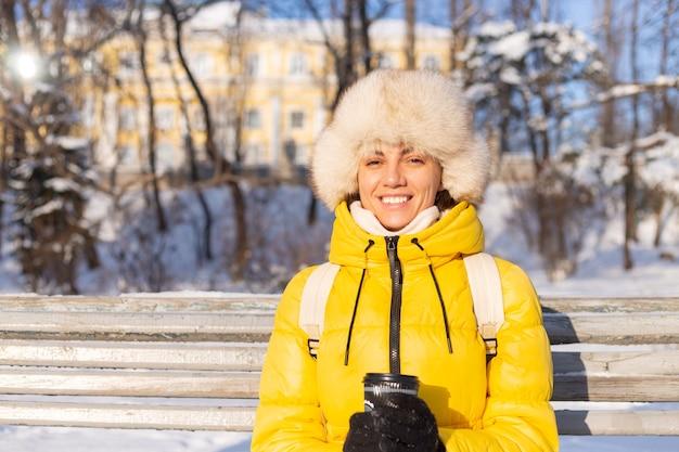 Heureuse jeune femme en hiver dans des vêtements chauds dans un parc enneigé par une journée ensoleillée est assise sur les bancs et profite de l'air frais et du café seul