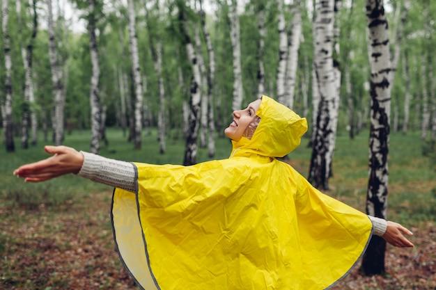 Heureuse jeune femme en imperméable jaune marchant dans la forêt de printemps et s'amusant en levant les bras