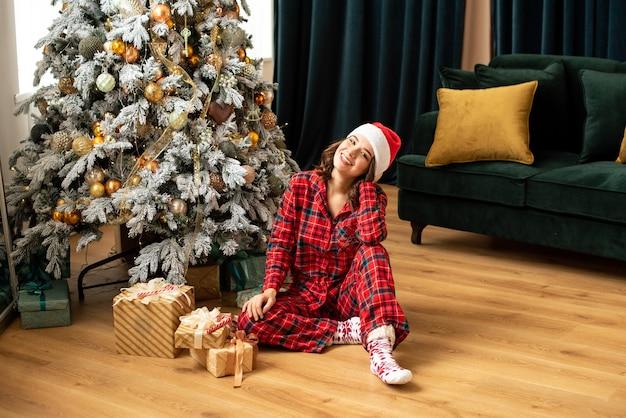 Heureuse jeune femme jetant un cadeau près de l'arbre de noël. elle est assise près des cadeaux et des cadeaux. couleurs tendance or fortuna et vert marée.