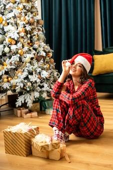 Heureuse jeune femme jetant un cadeau près de l'arbre de noël. elle s'asseyant près des cadeaux et du cadeau. couleurs tendance fortuna gold et tidewater green.