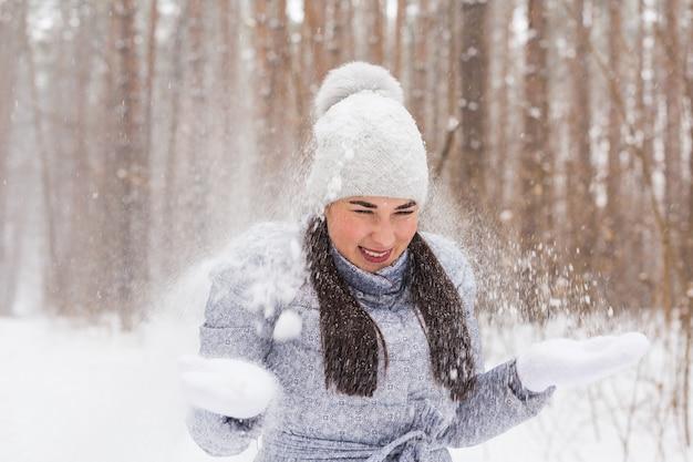 Heureuse jeune femme joue avec une neige à l'extérieur de la forêt enneigée.