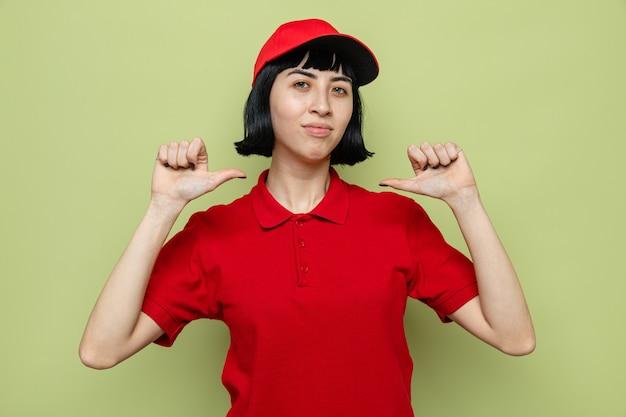 Heureuse jeune femme de livraison caucasienne pointant sur elle-même