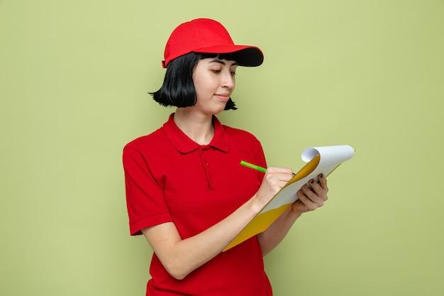 Heureuse jeune femme de livraison caucasienne tenant et écrivant sur le presse-papiers