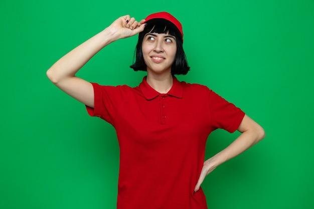 Heureuse jeune femme de livraison caucasienne tenant sa casquette et regardant de côté