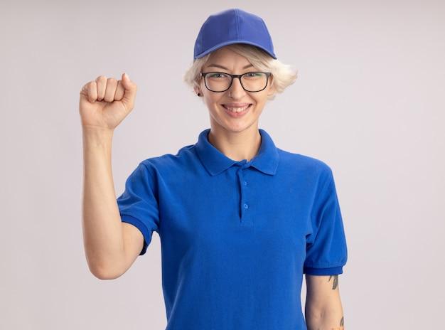Heureuse jeune femme de livraison en uniforme bleu et chapeau souriant confiant levant le poing debout sur un mur blanc