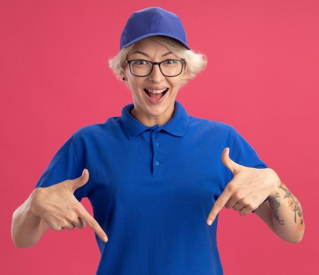Heureuse jeune femme de livraison en uniforme bleu et chapeau souriant joyeusement pointant avec l'index vers le bas sur le mur rose