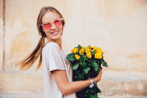Heureuse jeune femme à lunettes de soleil tient un bouquet de roses jaunes, posant à la caméra