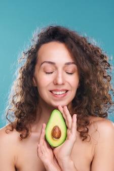 Heureuse jeune femme luxueuse avec sourire blanc à pleines dents tenant la moitié de l'avocat frais qui l'aide à prendre soin de la peau et du corps