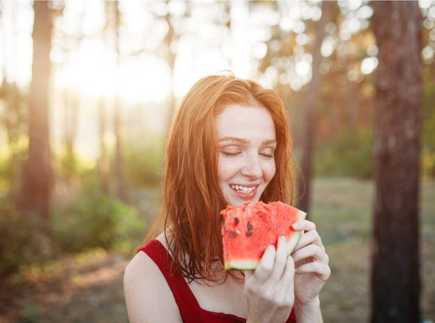 Heureuse jeune femme mangeant des pastèques sur la nature.