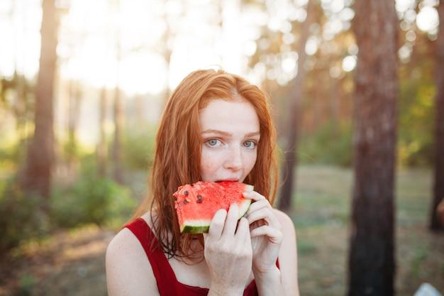 Heureuse jeune femme mangeant des pastèques