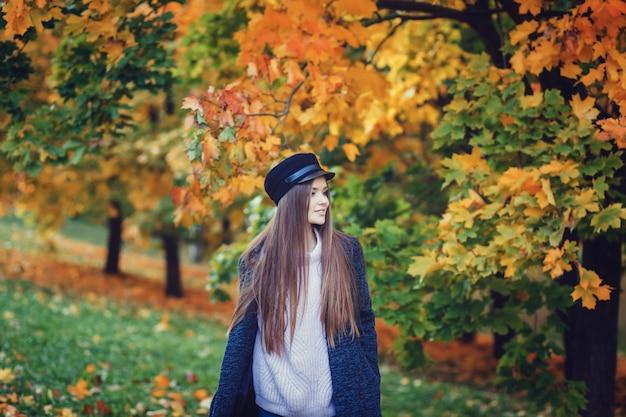 Heureuse jeune femme en manteau et chapeau noir