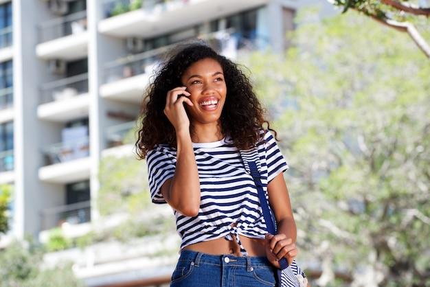 Heureuse jeune femme marchant et parlant au téléphone mobile à l'extérieur