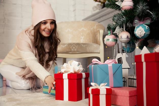 Heureuse jeune femme mettant des coffrets cadeaux sous le sapin de noël. cadeaux pour la famille. la fille au pull prépare une surprise.