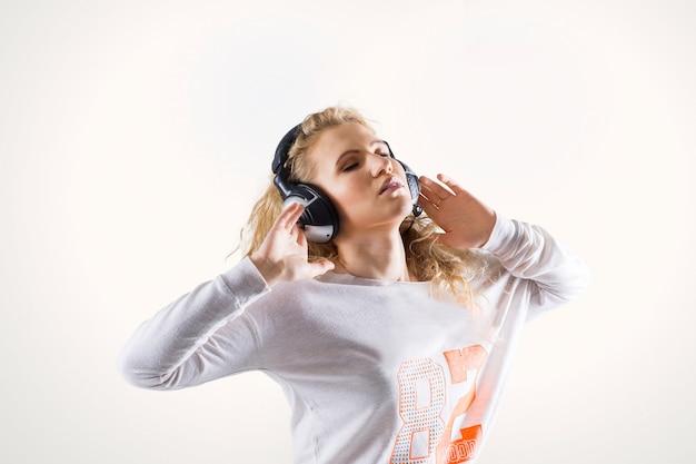 Heureuse jeune femme mignonne avec des écouteurs, écouter de la musique