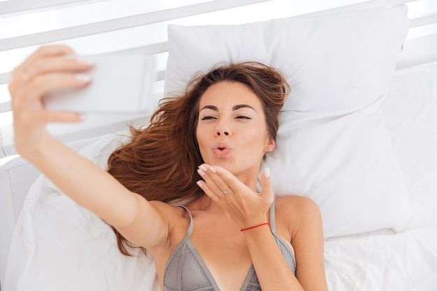 Heureuse jeune femme mignonne envoyant un baiser et prenant selfie avec smatphone