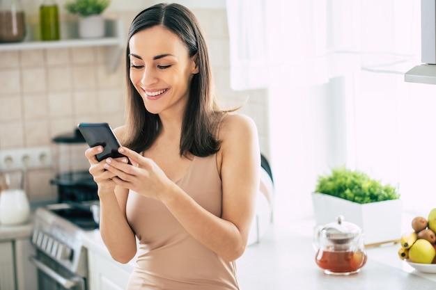 Heureuse jeune femme mignonne moderne se détendre tout en utilisant son téléphone intelligent dans la cuisine à la maison