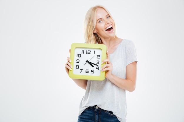 Heureuse jeune femme mignonne tenant une horloge murale sur un mur blanc