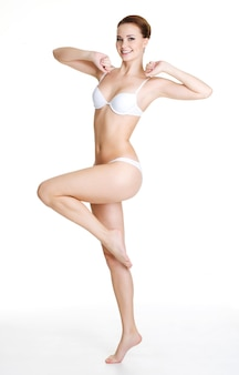 Heureuse jeune femme mince avec beau corps parfait posant sur blanc. portrait en pied
