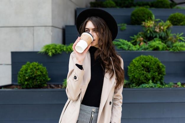 Heureuse jeune femme à la mode, boire du café à emporter et marcher après le shopping dans une ville urbaine.