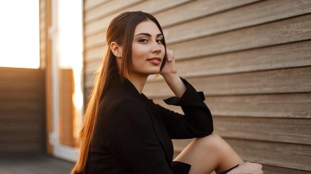 Heureuse jeune femme de mode dans un manteau noir se trouve près d'un mur vintage en bois au coucher du soleil