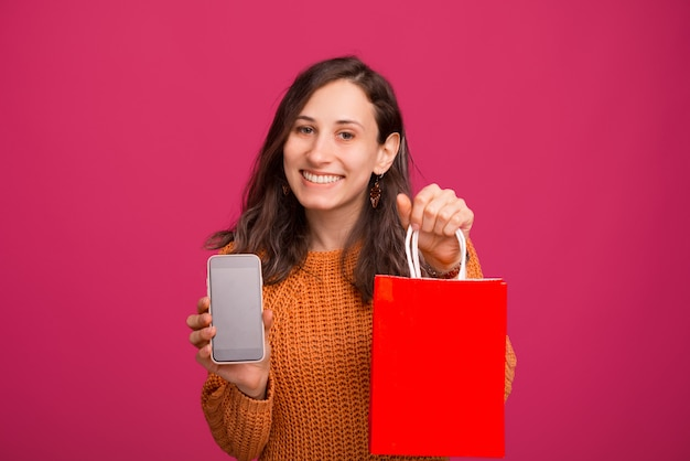 Heureuse jeune femme montrant l'écran du smartphone et tenant un sac à provisions rouge sur l'espace rose